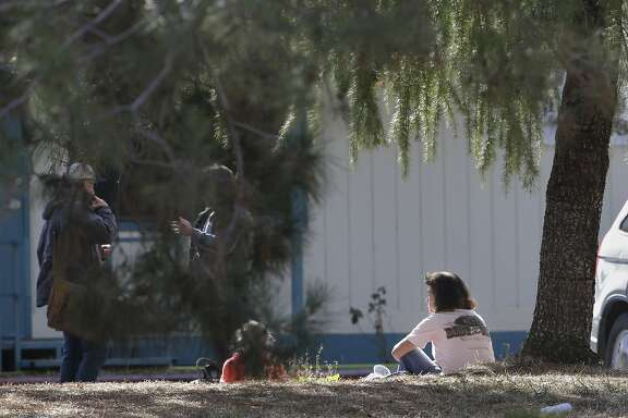 A woman and a child sit by an elementary school where a gunman opened fire in the community of Rancho Tehama Reserve in Corning, Calif., Tuesday, Nov. 14, 2017. The gunman choosing targets at random opened fire in the rural Northern California town Tuesday, killing several people at several sites and wounding others at the elementary school before police shot him dead, authorities said. (AP Photo/Rich Pedroncelli)