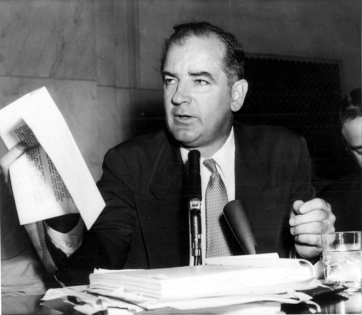 Sen. Joseph McCarthy (R-Wis) holds a copy of a letter under discussion at May 5, 1954 McCarthy-Army hearing session. [The televised hearings began April 22, 1954.] A committee attorney quoted FBI Director J. Edgar Hoover as saying the letter produced by McCarthy yesterday was not a true copy of one written by Hoover to the Army. McCarthy stressed that the letter he produced was verbatim with the FBI report, except for deletion of security information. (PHOTO DATED 05 05 1954) CREDIT: ASSOCIATED PRESS