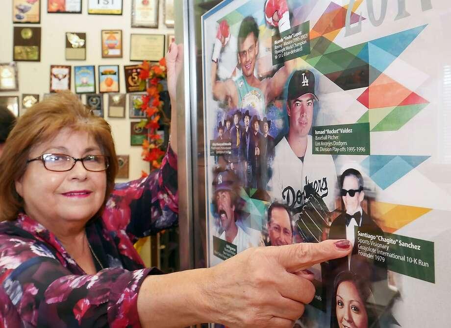 Gloria Sánchez, organizadora del Carrera del Guajolote 10K, aparece señalando la fotografía de su padre ya fallecido, Santiago Sánchez, quien fuera el fundador de la carrera en 1979. Él fue presentado en el Salón de la Fama de Latin American International Sports en el 2017. Photo: Foto Por Cuate Santos /Laredo Morning Times / Laredo Morning Times