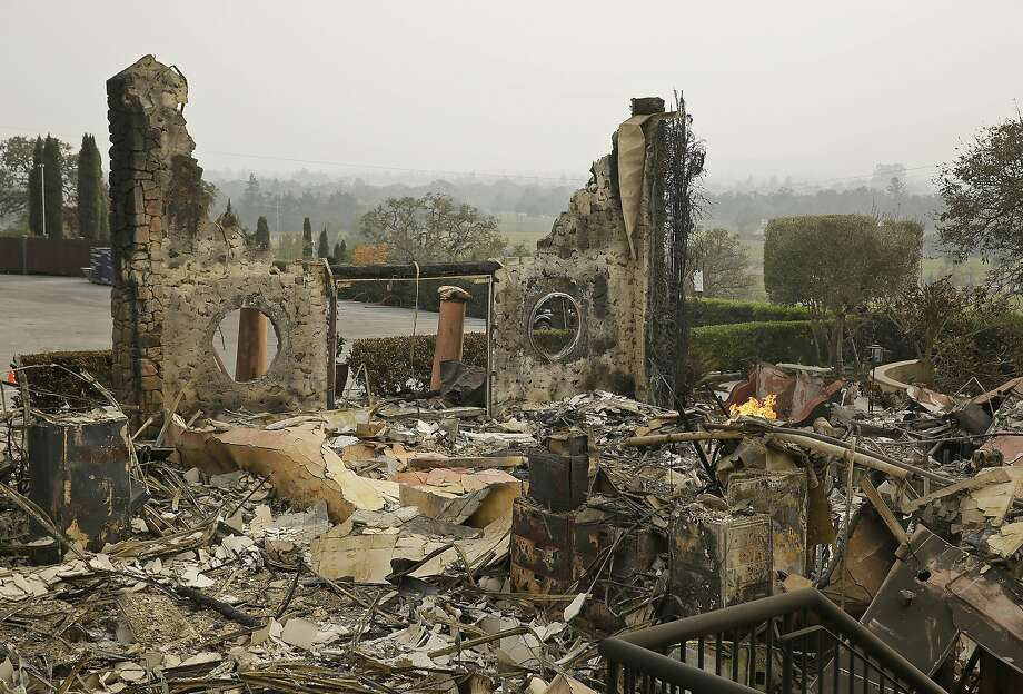 FILE - In this Oct. 10, 2017 file photo, the remains of the Signorello Estate winery continue to smolder in Napa, Calif. A month after deadly wildfires swept through California's famed wine country. Lost in the fire was the Napa winery�s signature stone hospitality building. A kitchen, corporate offices, a wine lab and the home of owner Ray Signorello Jr. also were destroyed. (AP Photo/Eric Risberg, File) Photo: Eric Risberg, Associated Press