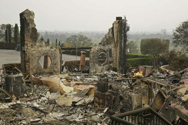 FILE - In this Oct. 10, 2017 file photo, the remains of the Signorello Estate winery continue to smolder in Napa, Calif. A month after deadly wildfires swept through California's famed wine country. Lost in the fire was the Napa winery�s signature stone hospitality building. A kitchen, corporate offices, a wine lab and the home of owner Ray Signorello Jr. also were destroyed. (AP Photo/Eric Risberg, File)
