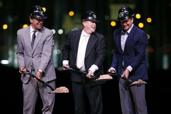 Raiders owner Mark Davis, center, poses for photographers beside Nevada Gov. Brian Sandoval, left, and NFL commissioner Roger Godell during a ceremonial groundbreaking for the Oakland Raiders' stadium Monday, Nov. 13, 2017, in Las Vegas. (AP Photo/John Locher)