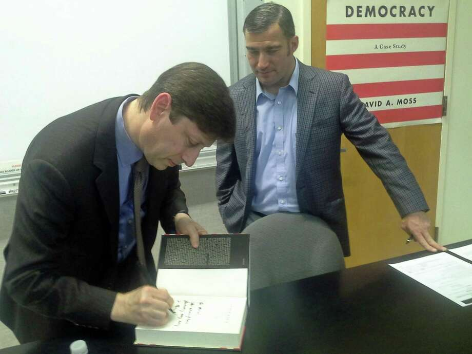 "Harvard professor David Moss signs a copy of his book ""Democracy: A Case Study"" for GHS U.S. History teacher Michael Gailatioto at the high school Tuesday."