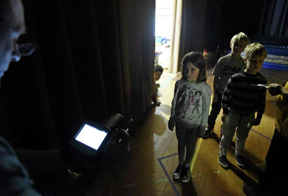 Former Lions Club President David Bonney, left, uses a machine to test first-grader Summer Jablonski's vision at the Lions Club of Greenwich free vision screening at North Street School in Greenwich, Conn. Tuesday, Nov. 14, 2017. The Lions Club has provided free vision tests for children for years now, but this is the first year that they will test all Greenwich public elementary school children. The tests are done quickly and accurately with a machine and are valuable especially for low-income students who might have difficulty seeing an optometrist. Photo: Tyler Sizemore / Hearst Connecticut Media / Greenwich Time