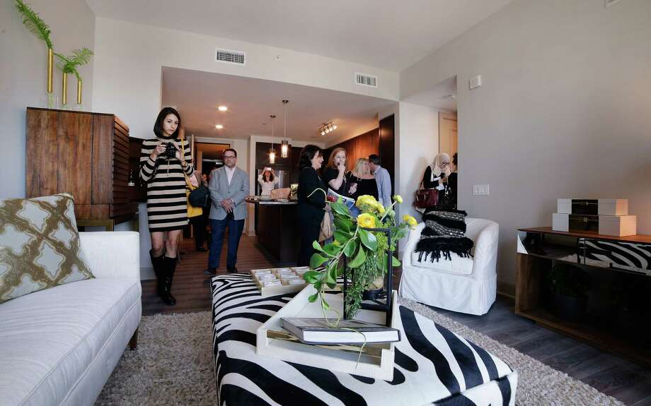 Tour attendants view the living area of a one bedroom residence on the 11th floor of the new Hotel ZaZa in Houston Nov. 14, 2017, in Houston, TX. (Michael Wyke / For the  Chronicle) Photo: Michael Wyke, Freelance / © 2017 Houston Chronicle