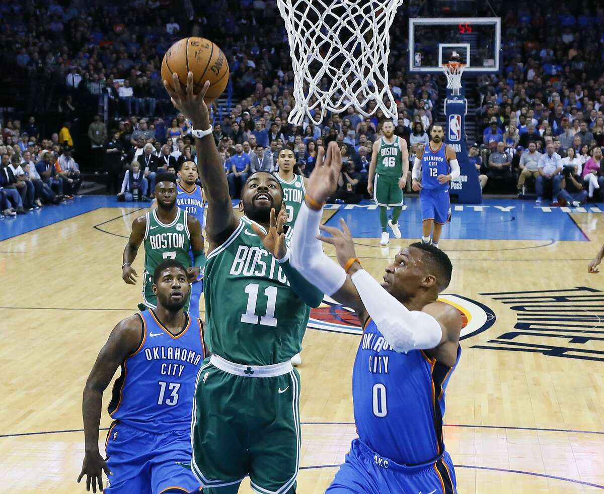 Boston Celtics guard Kyrie Irving (11) shoots between Oklahoma City Thunder forward Paul George (13) and guard Russell Westbrook (0) during the first quarter of an NBA basketball game in Oklahoma City, Friday, Nov. 3, 2017. (AP Photo/Sue Ogrocki)