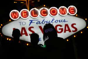 Runners stop to to have photos taken by official photographers at the Welcome to Las Vegas sign during the Rock 'n' Roll Las Vegas Marathon, Sunday, Nov. 12, 2017, in Las Vegas. (AP Photo/John Locher)