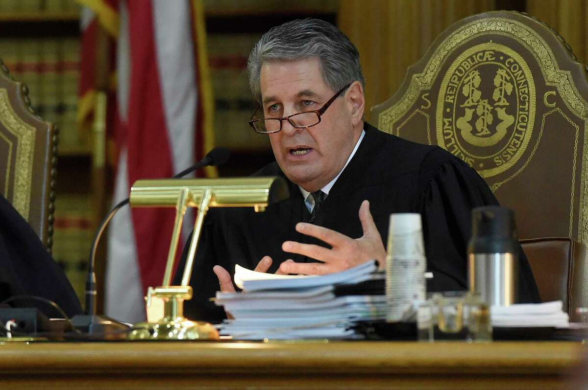 Justice Richard N. Palmer questions James Vogts, a lawyer for Remington Arms, during a hearing at the state Supreme Court in a lawsuit filed by Sandy Hook families against the company, in Hartford, Conn., Tuesday, Nov. 14, 2017. A survivor and relatives of nine people killed in the shooting are trying to sue the North Carolina company that made the AR-15-style rifle used to kill 20 first-graders and six educators at Sandy Hook Elementary School. A lower court dismissed the lawsuit. (Cloe Poisson/The Courant via AP, Pool)