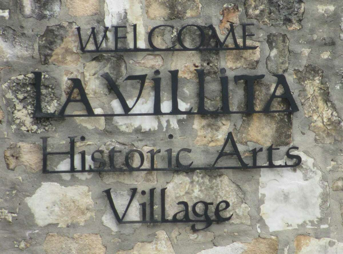 An iron sign on the corner of a stone wall welcomes guests to La Villita near South Alamo Street.