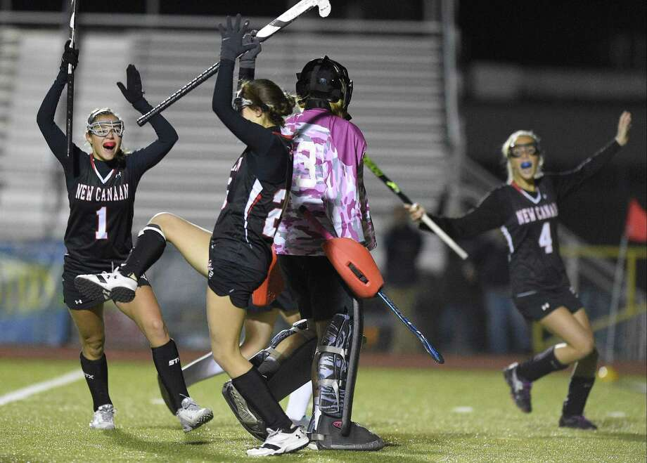 New Canaan Lauren Sturm (1) and Izzy Nesbett (4) react as Marlee Smith, center, celebrates her goal against Branford Tuesday night in a CIAC Class M field hockey semifinals at Trumbull High School. The Rams won, 2-1. Photo: Matthew Brown / Hearst Connecticut Media / Stamford Advocate
