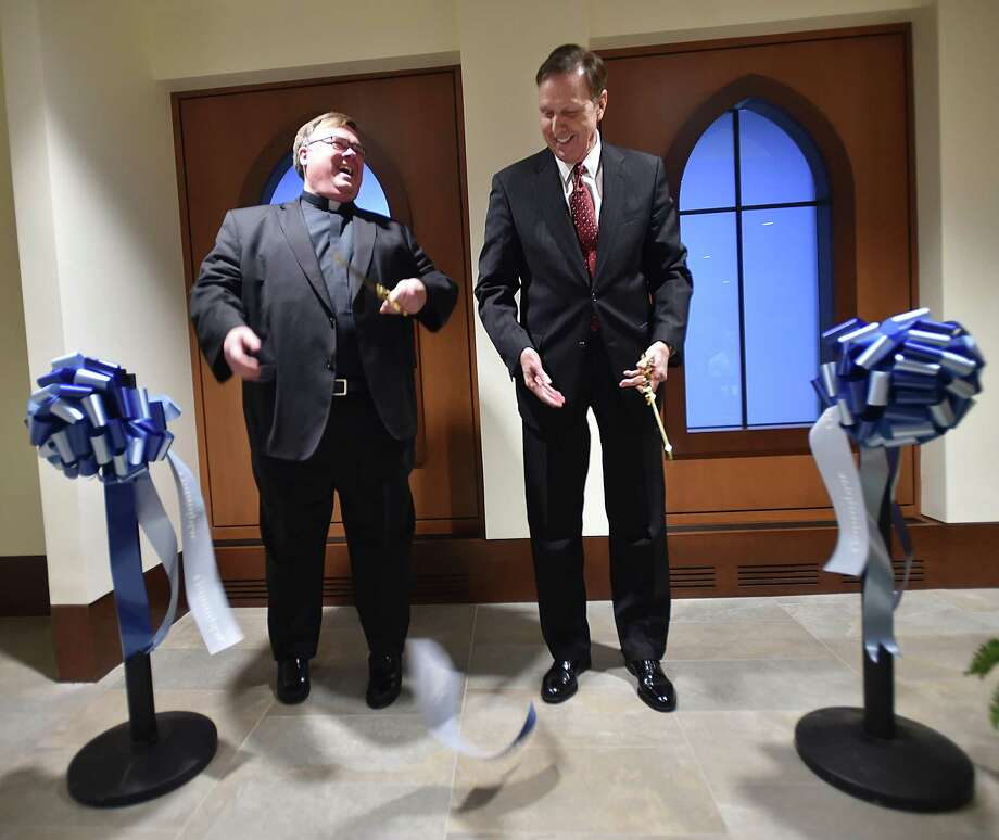 The Rev. Jordan Lenaghan, executive director of university religious life, and university President John L. Lahey cut the ceremonial ribbon to celebrate the opening of the Catholic chapel and Center for Religion Tuesday at Quinnipiac University in Hamden. Photo: Catherine Avalone / Hearst Connecticut Media / New Haven Register