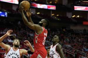Houston Rockets guard James Harden (13) drives to the basket scoring under the pressure of Toronto Raptors center Jonas Valanciunas (17) and Toronto Raptors forward Malcolm Miller (13), Tuesday, Nov. 14, 2017, at the Toyota Center in Houston.