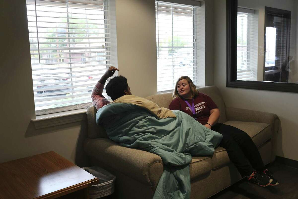 Alexandra Wheeler, residential specialist, helps a client at the Bridge Emergency Shelter of Roy Maas Youth Alternatives on Nov. 14, 2017. The nonprofit provides family counseling, emergency shelter and transitional living programs to homeless people 22 and under.