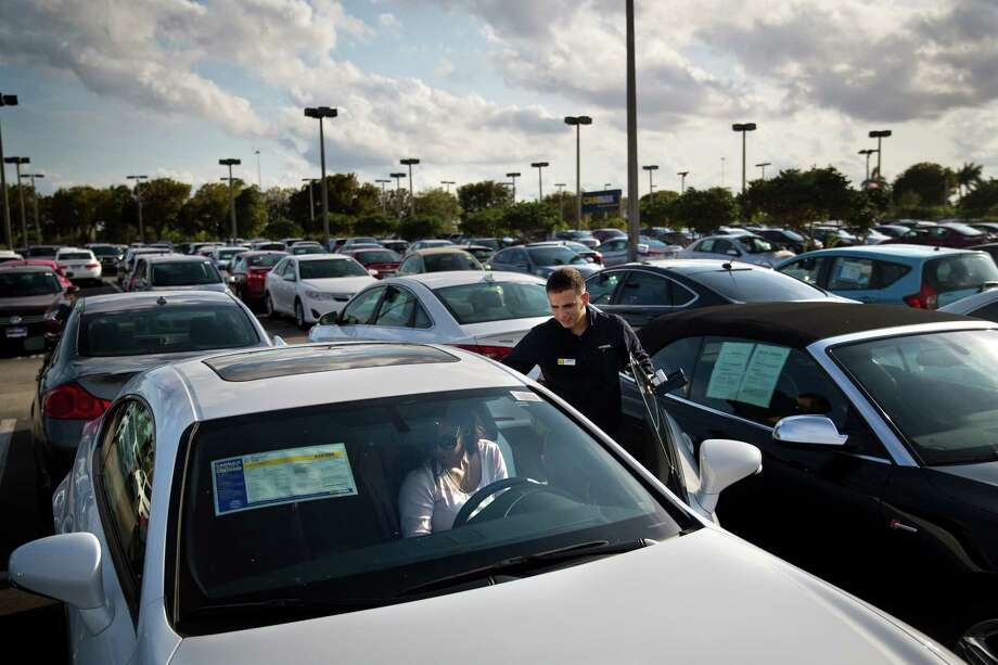 FILE-- A salesman helps customers at a Carmax dealer in Doral, Fla., March 13, 2017. On May 1, automakers reported the fourth straight monthly retreat in sales of new cars and light trucks, the longest stretch of declines since 2009, when the industry was embroiled in crisis and bankruptcies. The slump underscores the view of many that auto sales have peaked and are set to trend downward (Scott McIntyre/The New York Times) Photo: SCOTT MCINTYRE, STR / NYTNS
