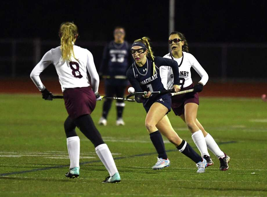Caroline Wax, of Immaculate, carries the ball between Granby Memorial's Kari Marks, left, and Heather Salter during the Class S Field Hockey state semifinal between Granby Memorial and Immaculate at Cheshire High 10/14/17. Photo: Krista Benson / The News-Times Freelance
