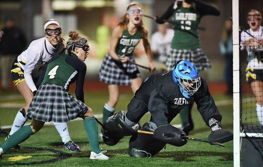 Hand's Erickson Richard battles Guilford's Mariah Cretella (4) and scores against goalkeeper Nicolette Spotlow and in the second half of the Class M field hockey semifinal game, Tuesday, Nov. 14, 2017, at the James L. MacVeigh Alumni Athletic Complex at Brandford High School. Hand won, 2-1, and will play New Canaan in the championship Saturday at Wethersfield High School. Photo: Catherine Avalone / Hearst Connecticut Media / New Haven Register