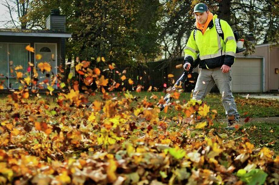 Kris Konechne uses a leaf blower to clear fallen leaves from his front yard on Tuesday in Midland. (Katy Kildee/kkildee@mdn.net)