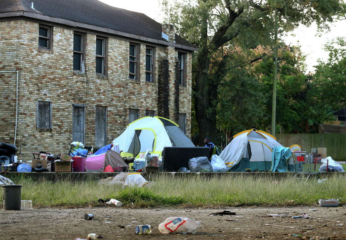 People moved their belongings to an empty lot as city officials conduct a cleanup of the homeless encampment that is located under the U.S. 59 Highway, between Caroline Street and Almeda Road Wednesday, Nov. 15, 2017, in Houston.