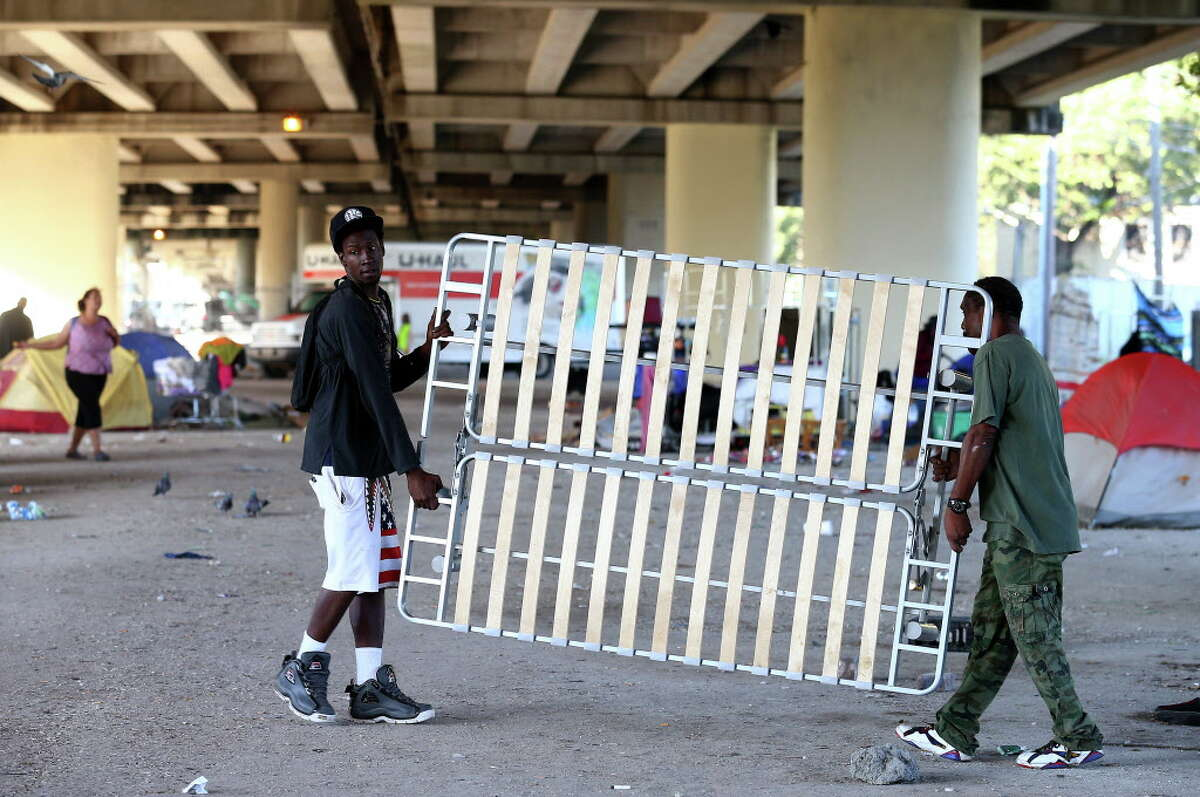 Nicholas Hudson, 31, left, helps a man move a sofa bed frame before city officials conducted a cleanup of the homeless encampment that is located under the U.S. 59 Highway, between Caroline Street and Almeda Road Wednesday, Nov. 15, 2017, in Houston. Hudson has been homeless after Harvey.