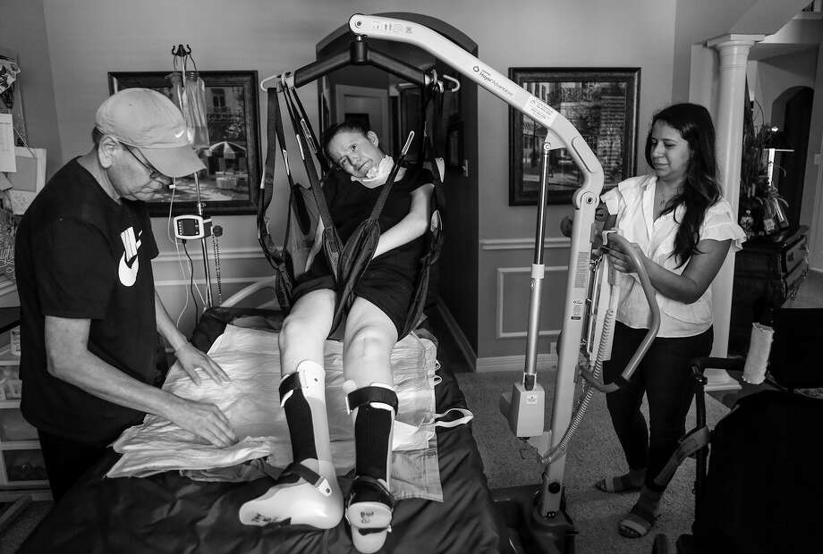 Al Coleman and his daughter Kristina Guilbeau lift Mandy Coleman out of her bed in the Coleman's dining room, Wednesday, Aug. 9, 2017, in Cypress. Photo: Mark Mulligan, Houston Chronicle / © 2017 Houston Chronicle