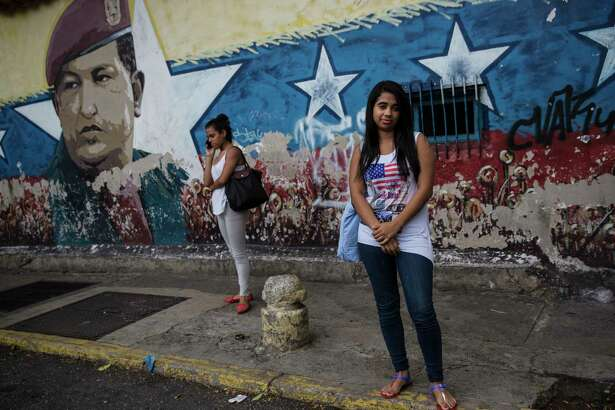Jenifer Rios, 16, poses for a portrait in front of a mural depicting former Venezuelan President Hugo Chavez, outside her school in Caracas, Venezuela, Saturday, Oct. 21, 2017. (AP Photo/Rodrigo Abd)