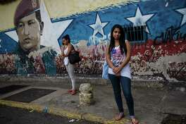 Jenifer Rios, 16, poses for a portrait in front of a mural depicting former Venezuelan President Hugo Chavez, outside her school in Caracas, Venezuela, Saturday, Oct. 21, 2017. (AP Photo/Rodrigo Abd)