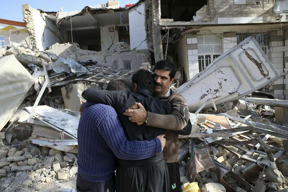 Earthquake survivors mourn in front of destroyed houses in Sarpol-e-Zahab in western Iran. Photo: Vahid Salemi, Associated Press