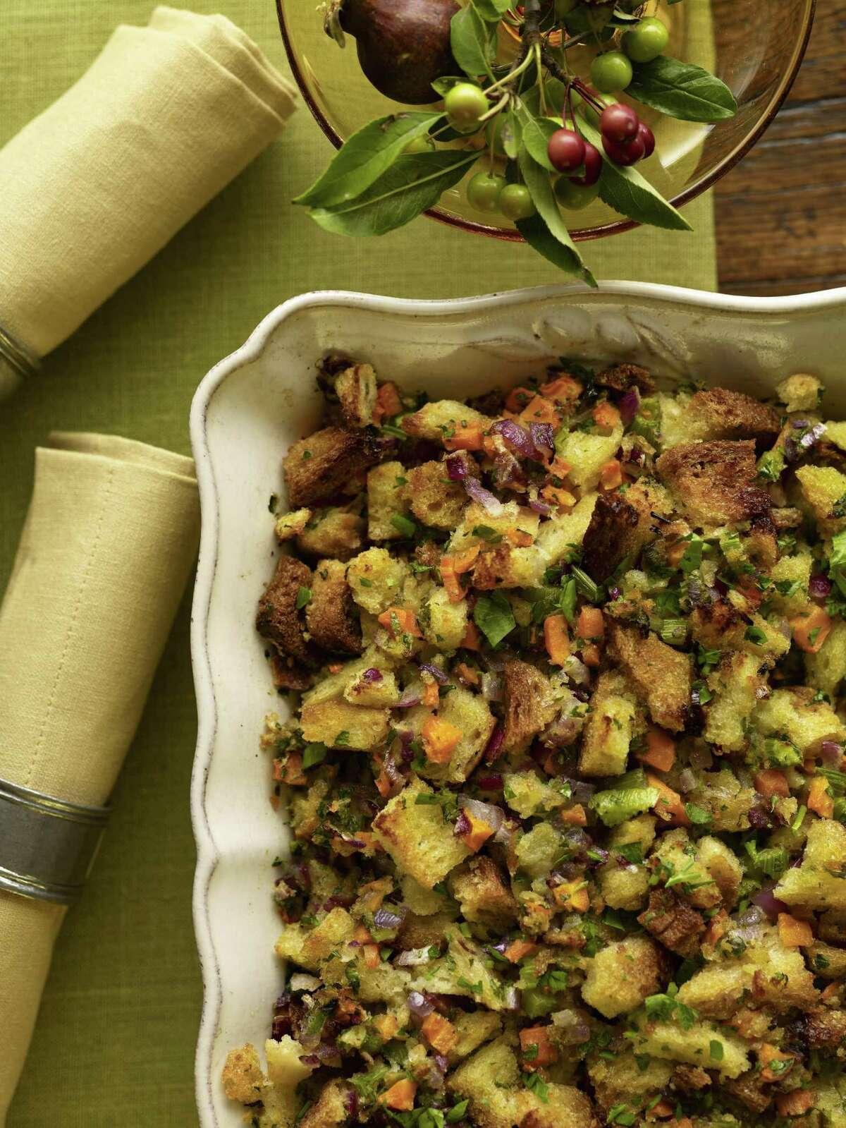Overhead shot of vegetable-herb stuffing in porcelain dish on green linen table runner