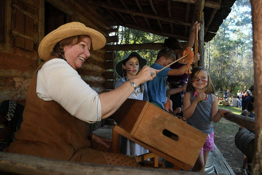 Demonstrator Betty Peters, from left, from the Celtaire String Band in Hockley, shows off a settler-era toy to Mary Brush, 7, of Houston, and Casdia Childers, 5, of Porter, at the Redbud Hill Homestead at Jesse H. Jones Park & Nature Center in Humble on Nov. 12, 2017. (Photo by Jerry Baker/Freelance) Photo: Jerry Baker, Freelance / Freelance
