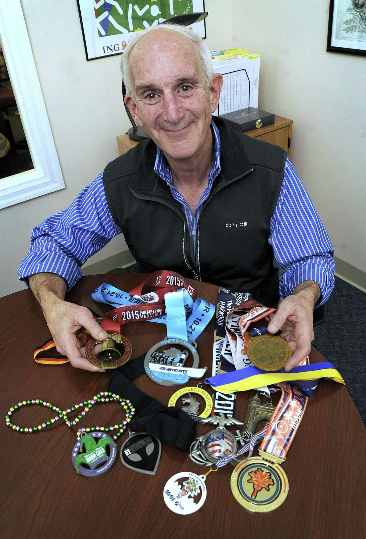 Bill Gross, 64, of Ridgefield, a marathon runner, with some of his medals. Gross is the owner and director of the Brookfield Learning Center.