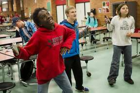 From left, Destiny Laws, 12, Tanner Bowerson, 16, and Bryson Bennett, 11, play Just Dance 2 on the Wii during The ROCK, a daily after-school program featuring snacks, tutors, crafts and games, on Wednesday, Nov. 15, 2017 at Jefferson Middle School. (Katy Kildee/kkildee@mdn.net)