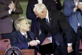 Texas Governor Greg Abbott, left, shakes hands with Vice President Mike Pence during a prayer vigil for the victims of the Sutherland Springs First Baptist Church shooting Nov. 8 in Floresville. Wednesday, Pence returned to Texas to get a briefing on Harvey recovery efforts and to address the Republican Governors Association in Austin.