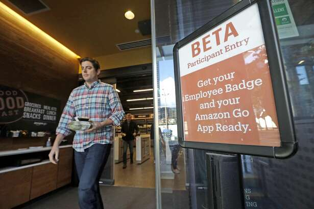 In this photo taken Wednesday, Oct. 11, 2017, a man walks out of an Amazon Go store, currently only for Amazon employees, in Seattle. (AP Photo/Elaine Thompson)