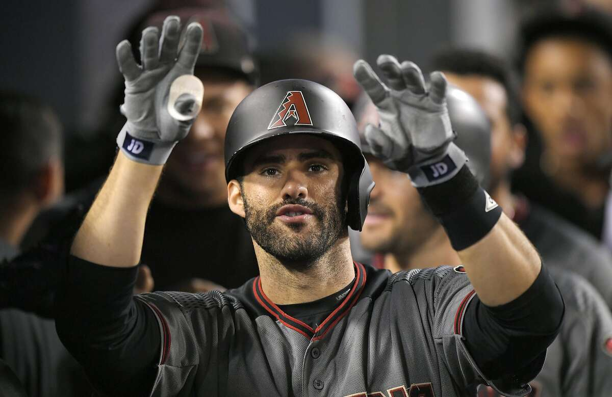 Arizona Diamondbacks' J.D. Martinez gestures toward the camera as he stands in the dugout after hitting his fourth home run of the game in the ninth inning of a baseball game against the Los Angeles Dodgers, Monday, Sept. 4, 2017, in Los Angeles. (AP Photo/Mark J. Terrill)