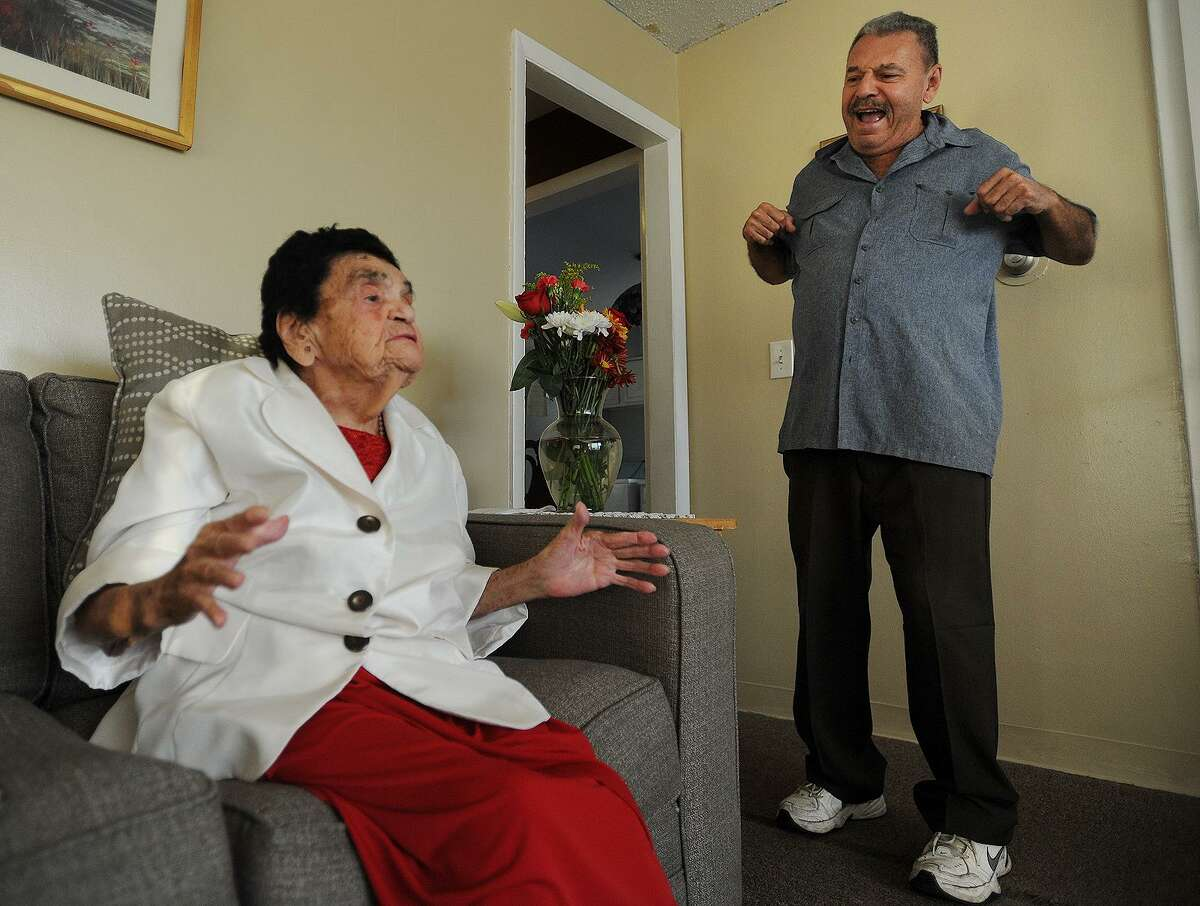 Along with her son, Juan Antonio Agosto, Ernesta Garcia, who just turned 107-years-old, demonstrates her daily exercises in her apartment in Bridgeport, Conn. on Thursday, November 9, 2017.
