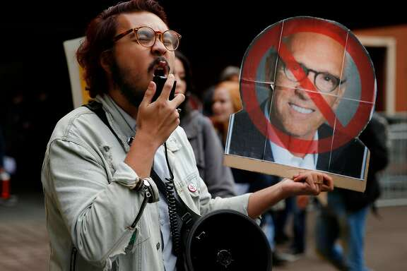 Justin Deckard, who holds a cardboard head of UC regent Norman Pattiz, protests outside the William J. Rutter Center as the Regents of the University of California meet inside, Wednesday, Nov. 15, 2017, in San Francisco, Calif. Demonstrators demanded the resignation of one of the regents, Norman Pattiz. Deckard comes from the UCSB student activist network.