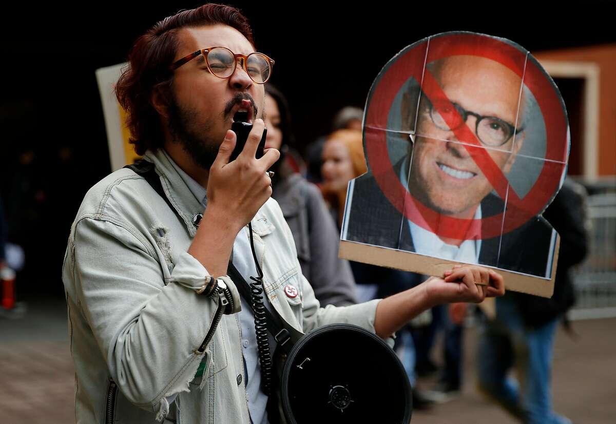 Justin Deckard holds a cardboard cutout of UC Regent Norman Pattiz at a rally calling for Pattiz to resign a year after he made lewd comments to an actress.