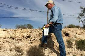 USGS scientist Bradley Van Gosen examines rock layers for the newly discovered mineral finchite near Lamesa. Van Gosen was the first to recognize the existence of the new mineral, which was named for longtime USGS uranium geologist Warren Finch.