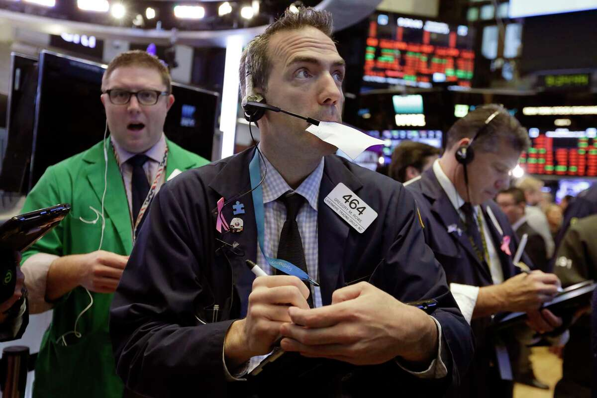 Trader Gregory Rowe, center, works on the floor of the New York Stock Exchange, Wednesday, Nov. 15, 2017. U.S. stocks declined in early trading Wednesday as investors weighed a batch of economic data and company earnings. (AP Photo/Richard Drew)