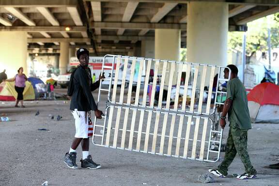 Nicholas Hudson, 31, left, helps a man move a sofa bed frame before city officials conducted a cleanup of the homeless encampment that is located under the U.S. 59 Highway, between Caroline Street and Almeda Road Wednesday, Nov. 15, 2017, in Houston. Hudson has been homeless after Harvey. ( Godofredo A. Vasquez / Houston Chronicle )