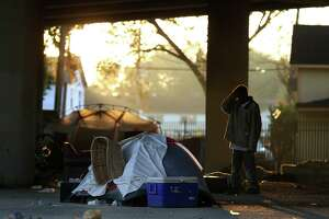 A man stands in front of his tent before having to move his belongings so that City officials conduct a cleanup of the homeless encampment that is located under the U.S. 59 Highway, between Caroline Street and Almeda Road Wednesday, Nov. 15, 2017, in Houston. ( Godofredo A. Vasquez / Houston Chronicle )