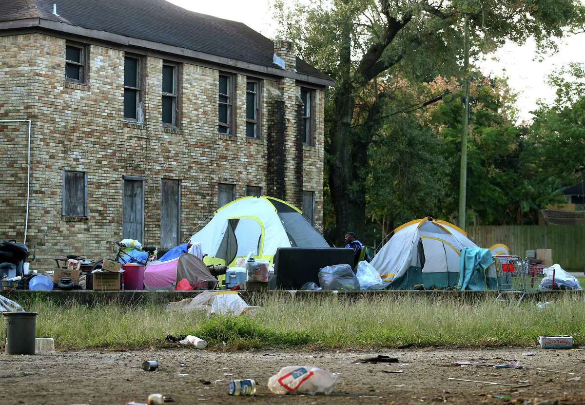 People moved their belongings to an empty lot as city officials conduct a cleanup of the homeless encampment that is located under the U.S. 59 Highway, between Caroline Street and Almeda Road Wednesday, Nov. 15, 2017, in Houston. ( Godofredo A. Vasquez / Houston Chronicle )