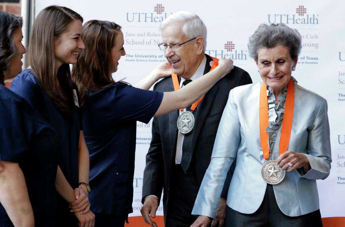 Nursing students Jennifer Valeasquez, from left, Emily Marso and Krista Robinson give medals to Robert and Jane Cizik for their $25 million donation.