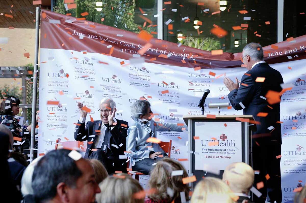 Confetti flies as a background is unveiled while Robert and Jane Cizik react along with UTHealth president Guiseppe Colasurdo (standing) during ceremonies to rename the nursing school to the Jane and Robert Cizik School of Nursing at UT Health Nov. 15, 2017, in Spring, TX. (Michael Wyke / For the Chronicle)