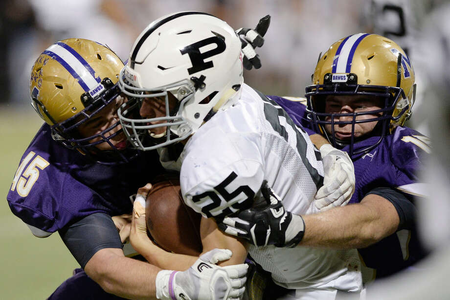 Midland High's Smith Essman (45) and Ross Marker (14) tackle Permian quarterback Steve Steen (25) on Oct. 13, 2017, at Grande Communications Stadium. James Durbin/Reporter-Telegram