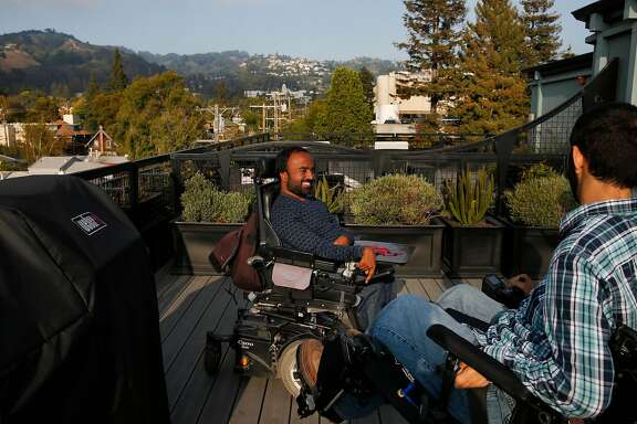 Alex Ghenis, right, shows Accomable co-founder and CEO Srin Madipalli the roof during a tour of his apartment for the Chronicle August 23, 2017 in Berkeley, Calif. Ghenis is putting his apartment up on Accomable.