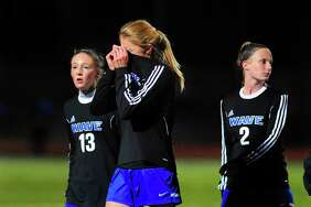 Darien's Katie Ramsay, center, walks off the field with teammates losing 3-2 to Staples in Class LL girls soccer semifinals.