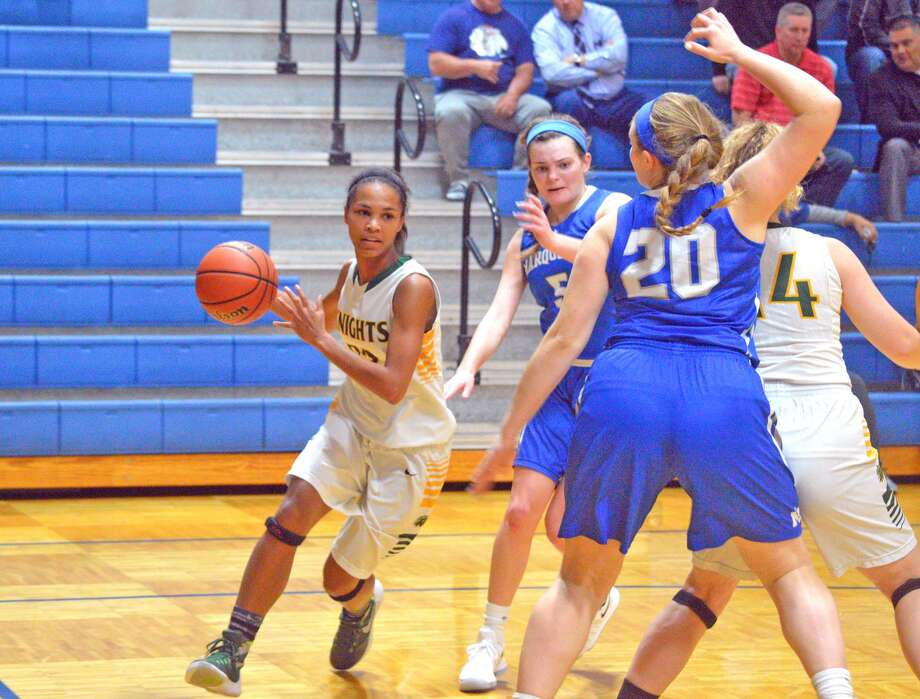 Metro-East Lutheran junior Ellen Schulte, left, drives to the basket during the second quarter of Wednesday's game against Alton Marquette at the Columbia Tip-Off Classic.