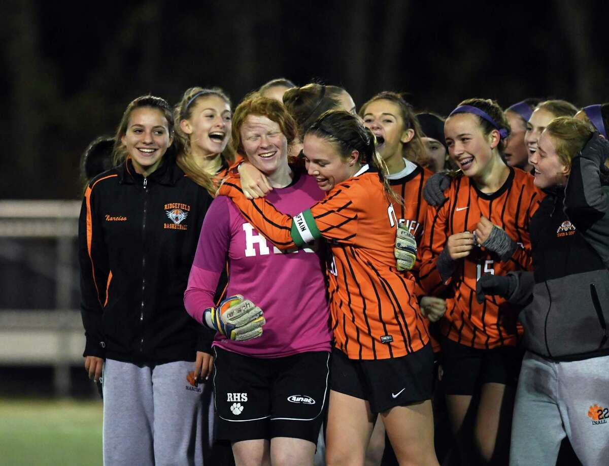 Erika Linke, right, hugs goalkeeper Lauren Castle, in pink, as the rest of the Ridgefield soccer team celebrates their win over Glastonbury.