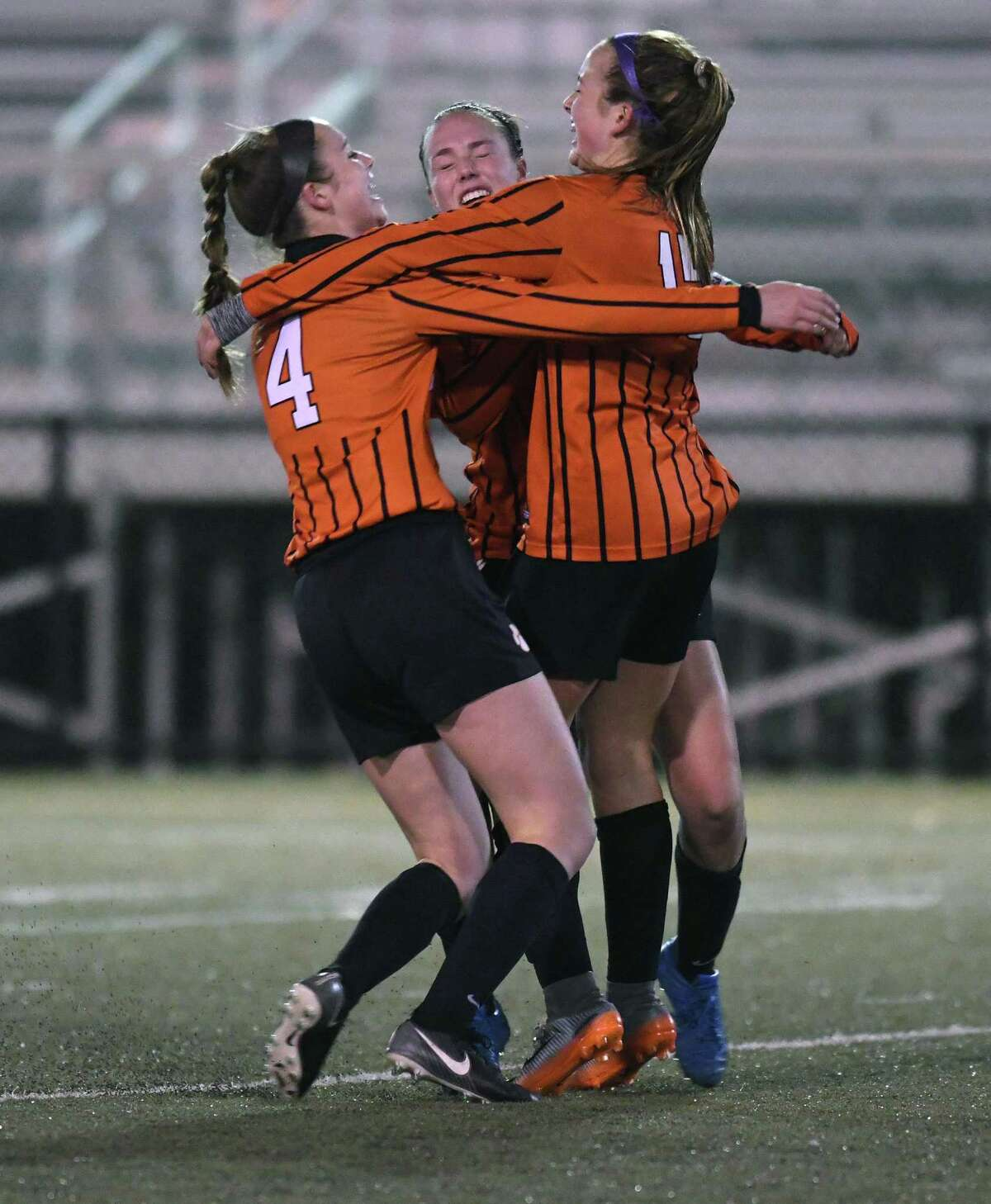 From left, Ridgefield?'s Claire Middlebrook, (4) and Erika Linke celebrate Faith Arnold?'s successful penalty kick that sealed Ridgefield?'s win in the Class LL state girls soccer semifinal between Ridgefield and Glastonbury at Municipal Stadium in Waterbury 10/15/17.